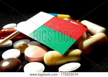 Malagasy Flag With Lot Of Medical Pills Isolated On Black Background