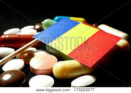 Romanian Flag With Lot Of Medical Pills Isolated On Black Background