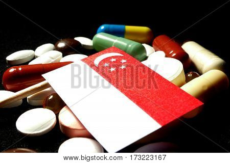 Singaporean Flag With Lot Of Medical Pills Isolated On Black Background
