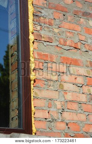 Close up on bricklaying detail with window frame thermal insulation with foam on house wall construction.