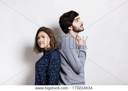 A horizontal portrait of two young people standing back to back having thoughtful expression. A stylish young bearded man holding his finger on his neck looking up thinking standing back to his girl