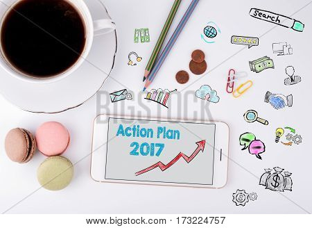 Action Plan 2017 Concept. Mobile phone and coffee cup on a white office desk.