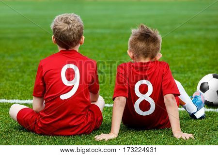Young Football Players. Young Soccer Team Sitting on Grass. Boys in Red Soccer Jersey Sitting on the Sports Pitch. Children Soccer Match. Football Sports Background
