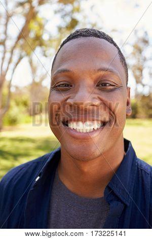 Outdoor Head And Shoulders Portrait Of Man In Park