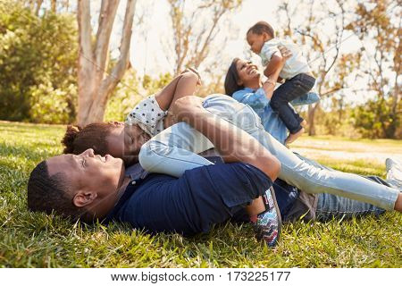 Parents Playing With Children On Grass In Summer Park