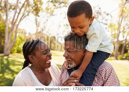 Grandparents And Grandson Having Fun In Park Together