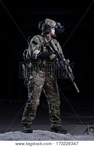 SWAT officer with a night vision device body armor and helmet with rifle in hands on dark background