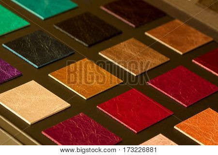 Colorful samples of leather on dark background, choice of texture and color