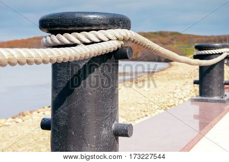 fence made of obsolete boat chain elements with sea ocean in background