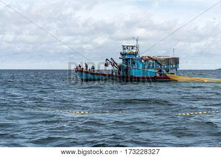 Fishing boat big fishermen with fish huge net on the blue ocean thailand catching fish