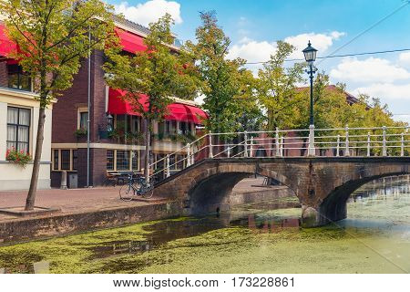 The picturesque bridge with a lantern through the canal and typical houses on a sunny day in Delft, South Holland, Netherlands.