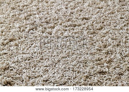 Light yellow shaggy carpet sample a closeup shot of rug background texture. Knitted fabric