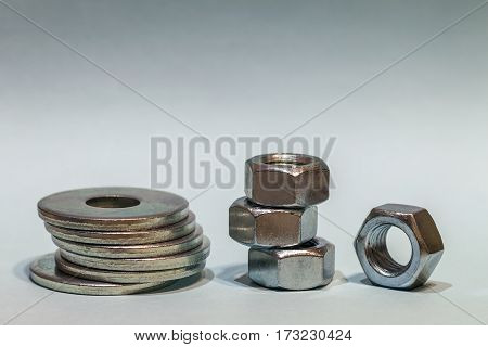 Joiner's accessories. Stacks of metal screw washers and nuts isolated on white background.