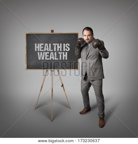 Health is wealth text on  blackboard with businessman wearing boxing gloves