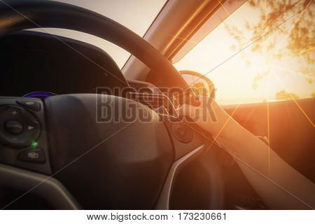 Close-up Of Woman's Hand Holding Steering Wheel with lens flare.