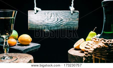 Retro-styled glass with sparkling wine and wine bottle. Fruit assortment on rustic boards. Wood sign hanging above fruit and wine. Isolated over black background