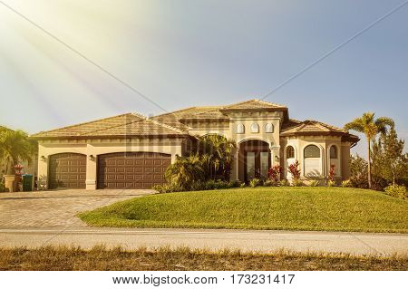 South Florida single family house in sunny day. Typical Southwest Florida concrete block and stucco home in the countryside with palm trees tropical plants and flowers grass lawn and pine trees. Florida.