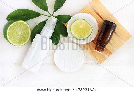 Natural cosmetics for home spa. Top view bottle of cream with water drops, essential oil, fresh lime fruit, green leaf decor, faded wooden background.