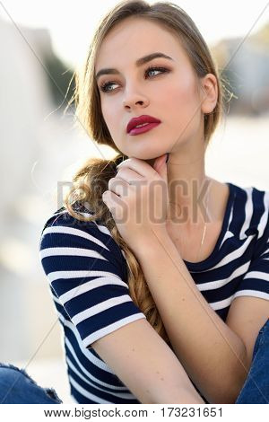 Blonde Woman, Model Of Fashion, Sitting In Urban Background.