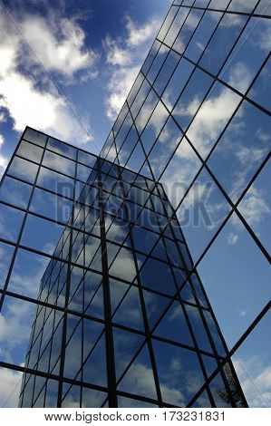 Detail of glass building for business reflection blue sky and clouds