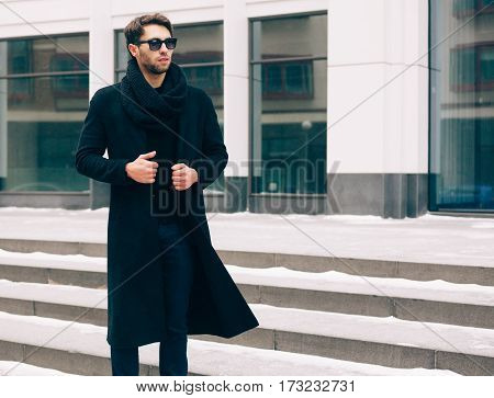 Elegant young handsome business man wearing suit and black coat posing against the background a business building. Fashion and Style. Streetstyle. Expectation.