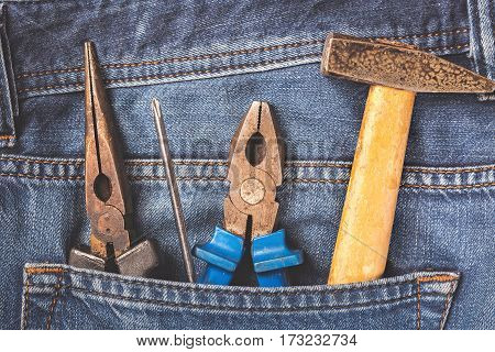 Working tools in jeans pocket. Close up.