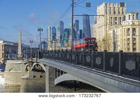 MOSCOW RUSSIA - JANUARY 21 2017: Red double-decker sightseeing bus on the Borodinsky bridge on the background of Moscow City skyscrapers. Moscow January sunny day.
