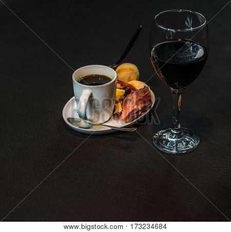 closse up view on a small snack consisting of meat and sausages French cheeses fresh crunchy bread black coffee and red wine with a tasty snack