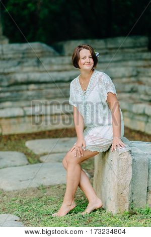 in the park barefoot woman in white openwork dress sitting on a rock