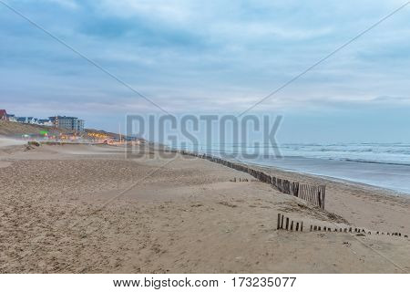 Stormy weather blows sand across the beach and roughens the surf at a seaside pavillion in Zandvoort Netherlands