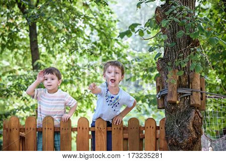 Two little brothers playing together standing on wooden playground in the summer park. Kid showing something interesting to his little brother. Young boy looking through imaginary tube.