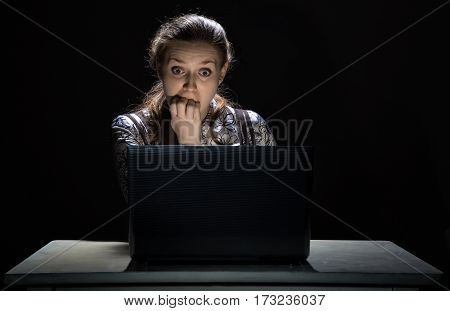 Scared woman watching movie on black background