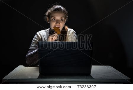 Woman watching movie and eating snack on black background