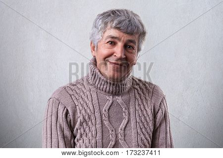 People and emotions. Portrait of an elderly man with gray hair and bright eyes full with happiness having pleasant smile looking into camera dressed in sweater isolated over white background