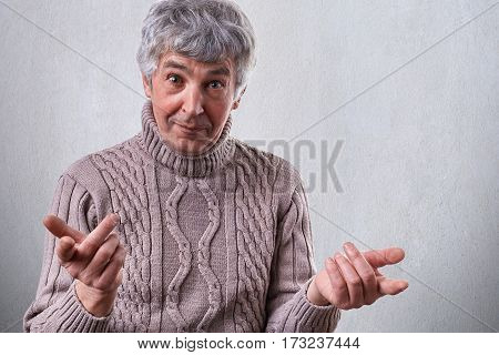 A photo of mature man dressed in sweater standing over white background having surprised expression holding his hands in front of him. Feeling confused. Emotions people emotions and lifestyle.