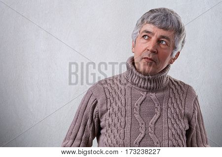 A portrait of attractive elderly man with wrinkles having thoughtful and pensive expression looking up wearing sweater. Lonely senior man thinking about his life. Old age problem and people concept.