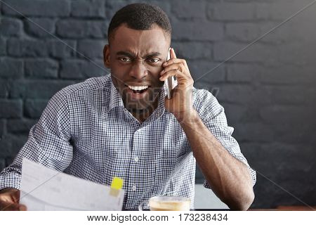 Furious And Mad Young African-american Businessman Shouting At Smart Phone, Having Conversation With