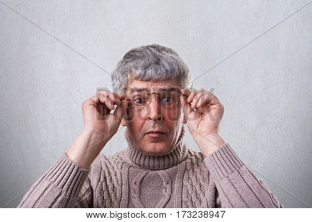 A close-up of astonished senior man wearing glasses and sweater holding his hands on the frames of glasses looking with wide opened eyes into camera. A surprised elderly man over white background
