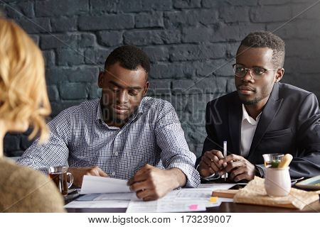 Two African Recruiters Interviewing Unrecognizable Woman Candidate: Man In Shirt Reviewing Curriculu