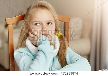 People And Lifetsyle. Portrait Of Sad Little Girl In Domestic Interior. Cute Blonde Female Child Wit