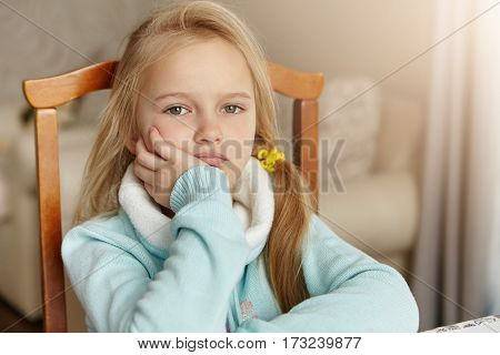 Beautiful Little Girl With Messy Hair Feeling Bored, Keeping Hand On Her Cheek, Sitting On Wooden Ch