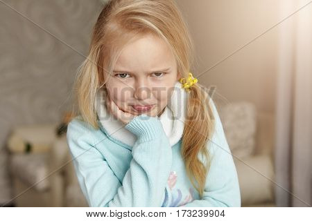 Indoor Shot Of Unhappy And Offended Blonde Caucasian Little Girl With Messy Hair Pouting Her Lips, B