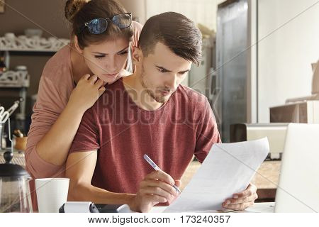 European Family Managing Domestic Finances At Home. Unemployed Man With Serious And Concentrated Loo