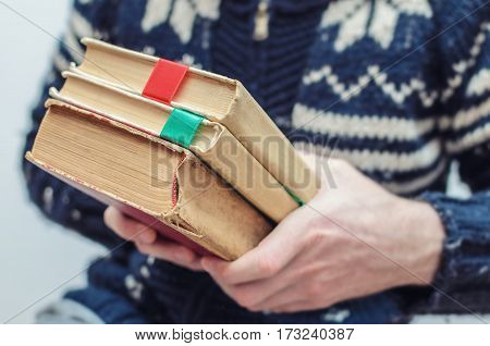 man holding an old book in his hands with a ribbon between the pages
