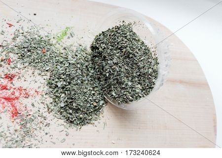 Jar with oriental spices were scattered on a light wooden board.
