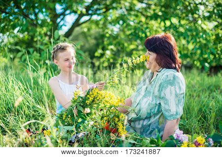 grandmother granddaughter with flowers in the green garden on a sunny summer day