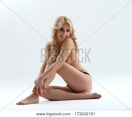 Beautiful curly blonde posing naked with a playful smile studio shot