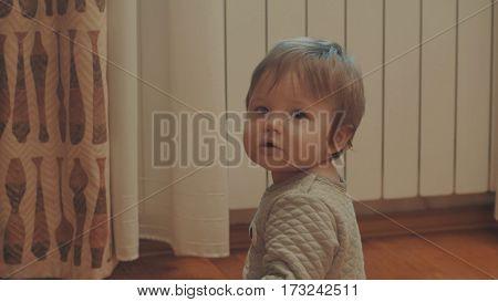 Little baby playing on the floor. Eye level shot