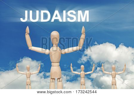 Wooden dummy puppet on sky background with text JUDAISM. Abstract conceptual image