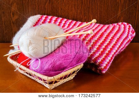 Basket with knitting needles and wool and knitted sweater. Selective focus